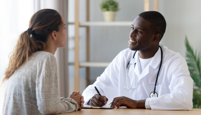 woman talking to smiling african black male doctor
